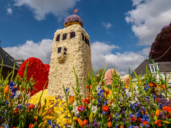 Endless row of floats on flower parade through the Dutch bulb fields lighthouse in Holland