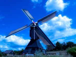 Cycling in Holland on the dykes along the river Linge by a watermill in Leerdam
